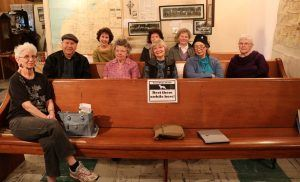 Historical Society Members Seated on Wooden Pews