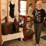Woman Standing by Roaring 20s Historical Artifacts Display